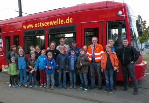 Jugendgruppe mit Begleitung vor Fahrschulwagen