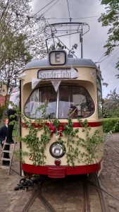 """Zwei Museumsstrassenbahner beim Schmücken des """"Hochzeitswagen""""."""